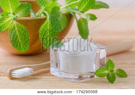 alternative natural toothpaste xylitol soda salt and wood toothbrush mint on wooden background poster