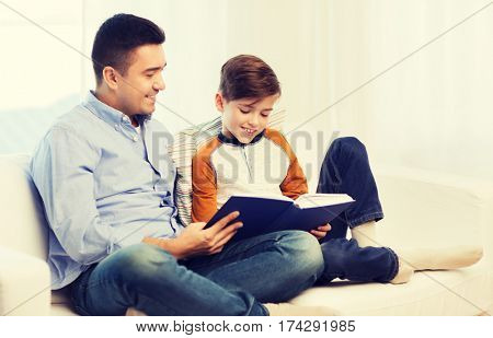family, fatherhood, generation, literature and people concept - happy father and son reading book at home
