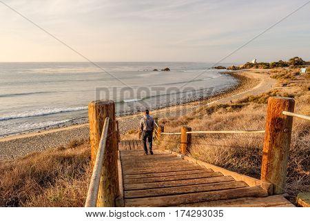 Man walking at boardwalk to Leo Carrillo State Beach, Malibu, California.
