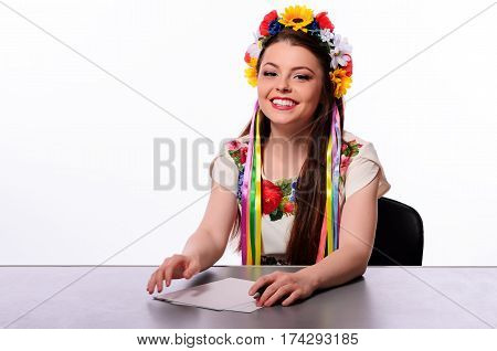 Happy Business Woman With Note And Pen By A Desk In The Ukrainian National Costume