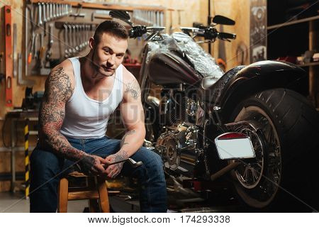 It is my bike. Serious muscular male sitting on the chair near big wheel holding spanner while posing in the garage