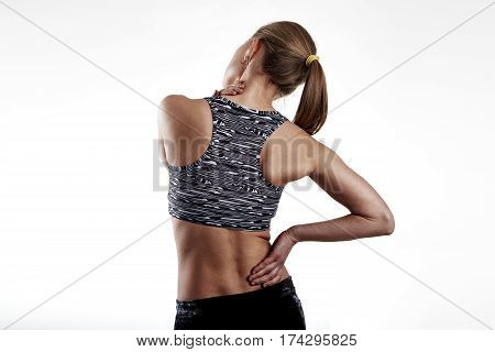 Fitness woman in sportswear touching her painful body. Rheumatism problem concept.