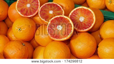 Ripe Oranges And An Orange Cut In The Stall Of Greengrocer