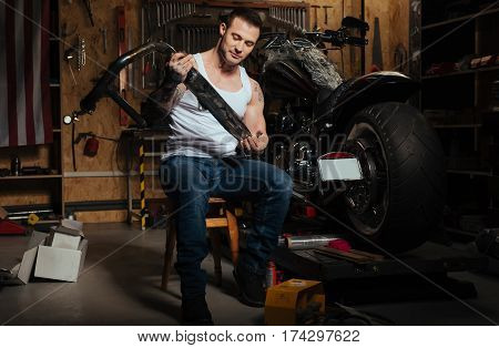 Positive thoughts. Attractive young master wearing jeans and white vest sitting on the chair while looking at exhaust tube
