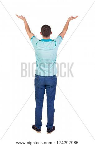 Back view of Beautiful man in jeans looking at wall and Holds  hand up.  young brunette standing. Rear view people. Isolated over white background.