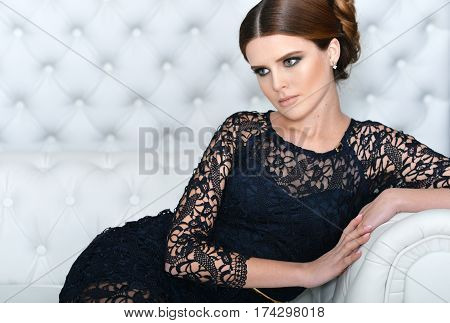 young gorgeous woman in black dress with beautiful make-up and hairdo