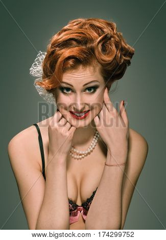 Beautiful retro woman with hairstyle and necklace grimacing and smiling