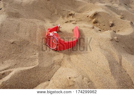 Red wrist watch for sports on the sand on the beach