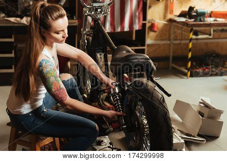 Save your bike. Beautiful brunette putting her hands on damper having big colorful tattoo on her right arm, sitting in semi position