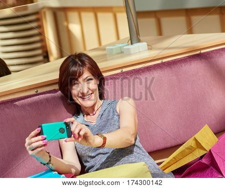 Smiling happy woman with paperbags making selfie after shopping