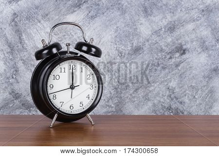 12 O'clock Vintage Clock On Wood Table And Wall Background