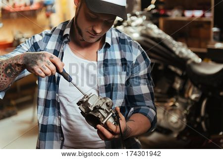 Check it. Attentive master wearing cap and checked shirt using screwdriver while fixing nuts