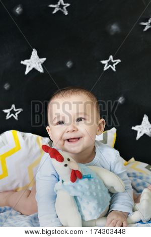 Cheerful toddler on a bed hugging a chicken stuffed toy. Vertical indoors shot.