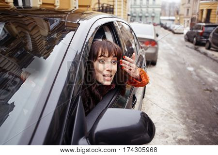 Woman demonstrating angry emotions while seating in car