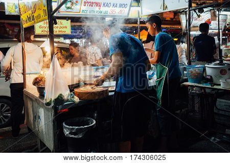 CHIANG MAI THAILAND - AUGUST 27: Father and sun cooking food at the Saturday Night Market on August 27 2016 in Chiang Mai Thailand.