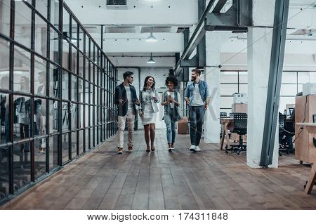 Young business professionals. Full length of young modern people in smart casual wear discussing business while walking through the office corridor
