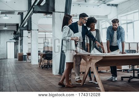 Passionate about their project. Group of young business people working together in creative office while standing near the wooden desk