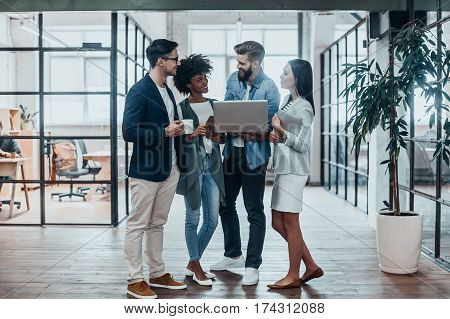 Quick meeting. Full length of young business people in smart casual wear working together and smiling while standing in the office hallway