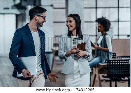 Sharing fresh office news. Two young colleagues in smart casual wear discussing business and smiling while walking through the office