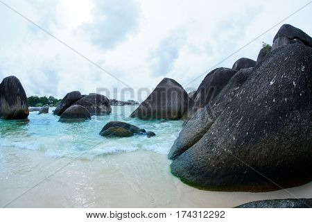 Natural black rock formation on the seashore at the beach in Belitung Island at daytime, Indonesia.