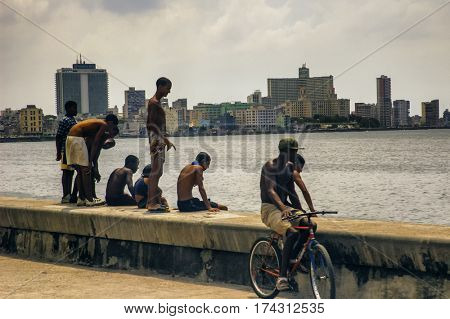 Havana, Cuba  - July 11, 2006. : Silhouette of young boys relaxing at sunset at the Malecon seawall in Havana