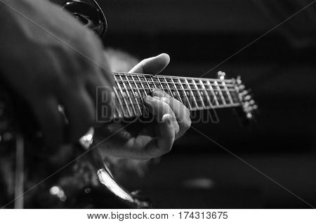 Guitar string close-up on a concert of rock music in the hands of a musician. guitarist