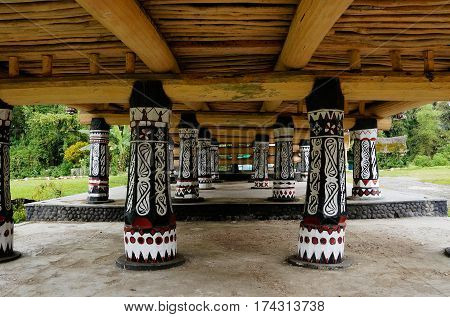 Black pillars with white drawings underneath a house at an old Batak village in Sumatra Samosir Island in the afternoon Indonesia