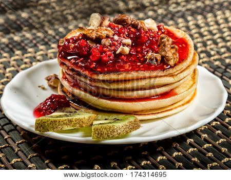Homemade sweet pancakes with raspberry jam on a white plate. Breakfast with stack topped blueberry jam, walnuts and kiwi.