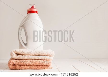Gel for laundry washing in a white unnamed plastic bottle, standing on a fresh colored towels. Composition on white wooden shelf. Light monochromatic empty for text background.