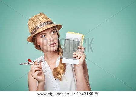 Closeup portrait of beautiful woman in straw hat holding airplane model and passport with tickets looking away in toughts at blank copy space