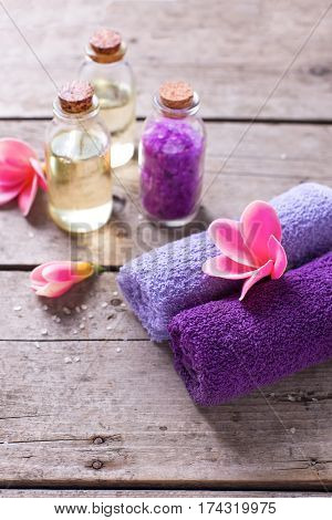 Spa setting. Towels bottles with oil and sea salt on vintage wooden background. Selective focus is on towels.