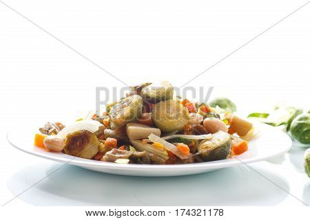 Brussels sprouts roasted with vegetables and beans on a plate