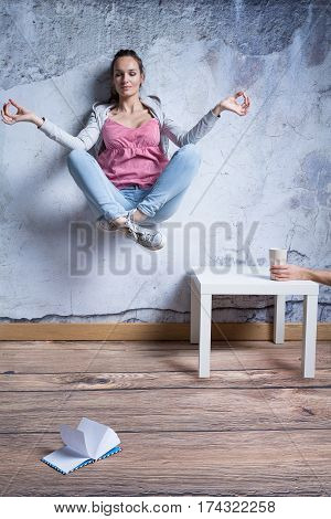 Meditating young woman levitating above a ground