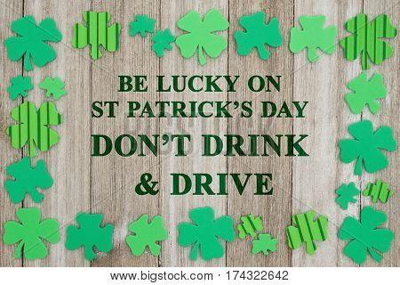 Saint Patrick's Day safety message Green shamrocks on weathered wood with text Be Lucky on St Patrick's Day Don't Drink and Drive