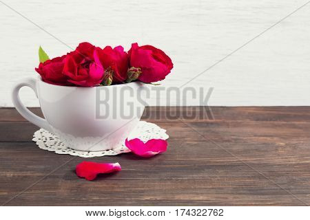 Small bouquet of red roses in a white cup on the wooden table. Warm toned photo.
