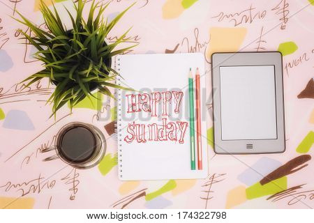 Coffee cup, ebook and notebook with an inscription: happy sunday