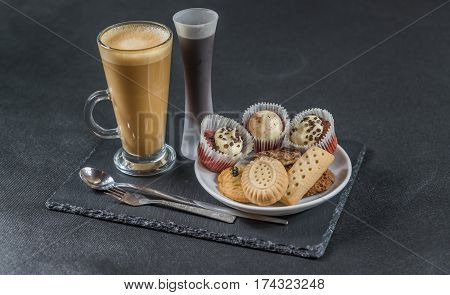 right side view on an aromatic coffee latte with three buttered muffins and petit fours on a white saucercoffee liqueur in a glass spoon and forks the whole on a black stone plate sweet set