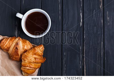 Coffee and croissants on the black table, top view