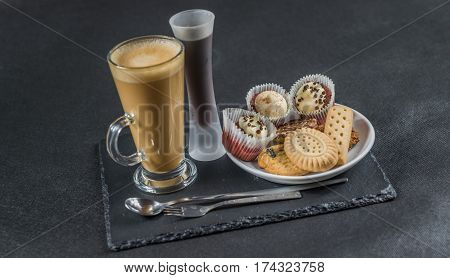 left side view on an aromatic coffee latte with three buttered muffins and petit fours on a white saucercoffee liqueur in a glass spoon and forks the whole on a black stone plate sweet set