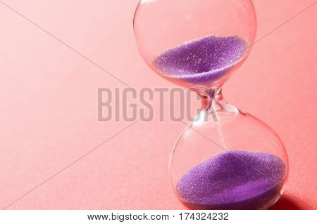 Purple sand clock is on bright red background.