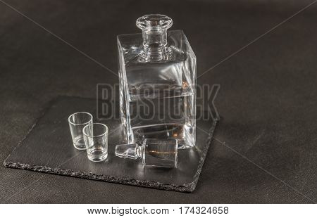 right side view on a pure vodka in crystal modern carafe with a beautiful stopper and two glasses the whole on a black stone plate drinks set