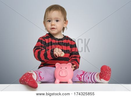 Little Child Is Putting Coins In Piggy Bank And Is Saving Money