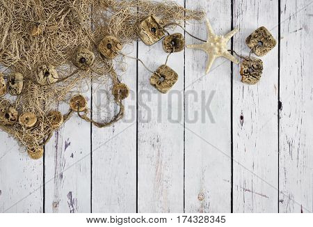 Fishing net or nautical vessel and starfish on wooden planks. Beach background or summer background with copy space.