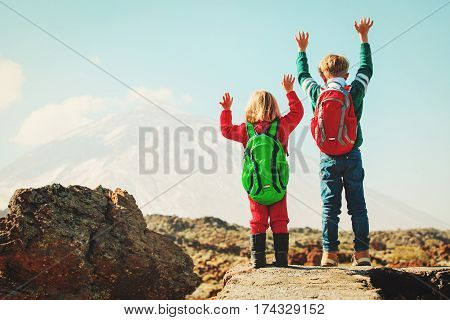 happy little boy and girl hiking in scenic mountains