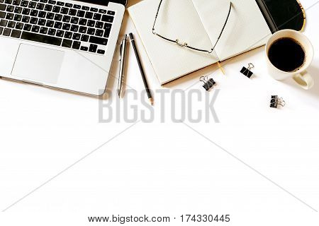 Modern minimalistic work place. White office desk table with laptop, coffee cup, clips, glasses, notebook, pen and penclil. Top view with copy space, flat lay