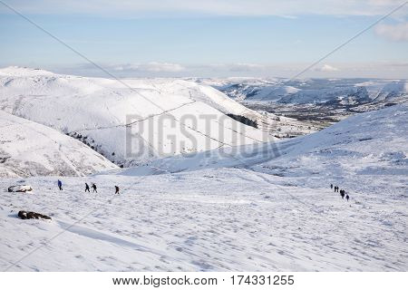 PEAK DISTRICT UK - CIRCA 2012: A group of hikers walking up Kinder Scout in winter with Edale valley in the distance. Peak District UK
