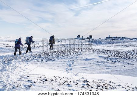 PEAK DISTRICT UK - CIRCA 2012: Group of hikers climb Kinder Scout in winter. Peak District UK.
