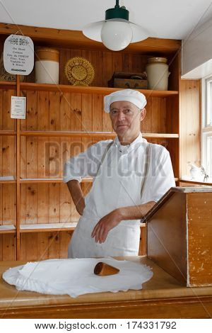 IRONBRIDGE UK - CIRCA 2013: Baker at the Victorian Bakery shop store in Blists Hill Museum Ironbridge Shropshire UK