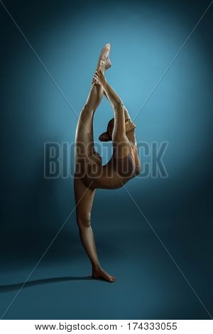 Full length side view shot of flexible slim woman with athletic bronzed body performing at studio, copy space