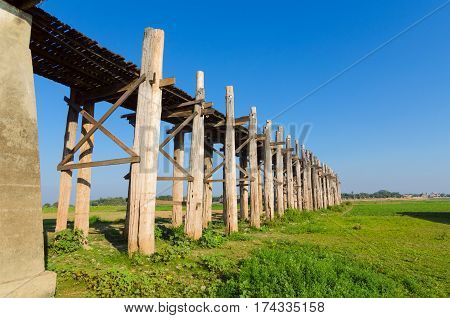 The longest bridge in the world with blue sky and green grass, U-Bein Bridge, Mandalay, Myanmar.